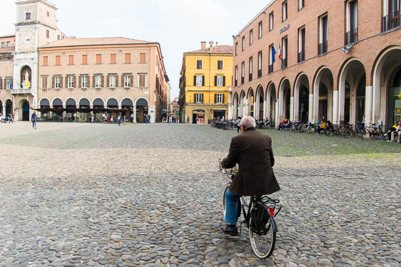 Man riding bicycle in Modena main square